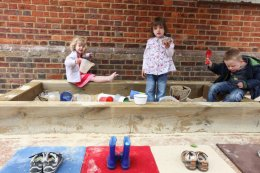 Children playing in sand pit at Montessori nursery