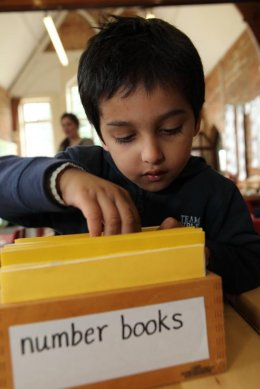 Finding a book at Montessori nursery in Wheeler End